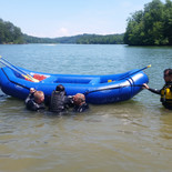 Instructor Benjamin demonstrating how two swimmers can assist a victim into a raft while in the water.