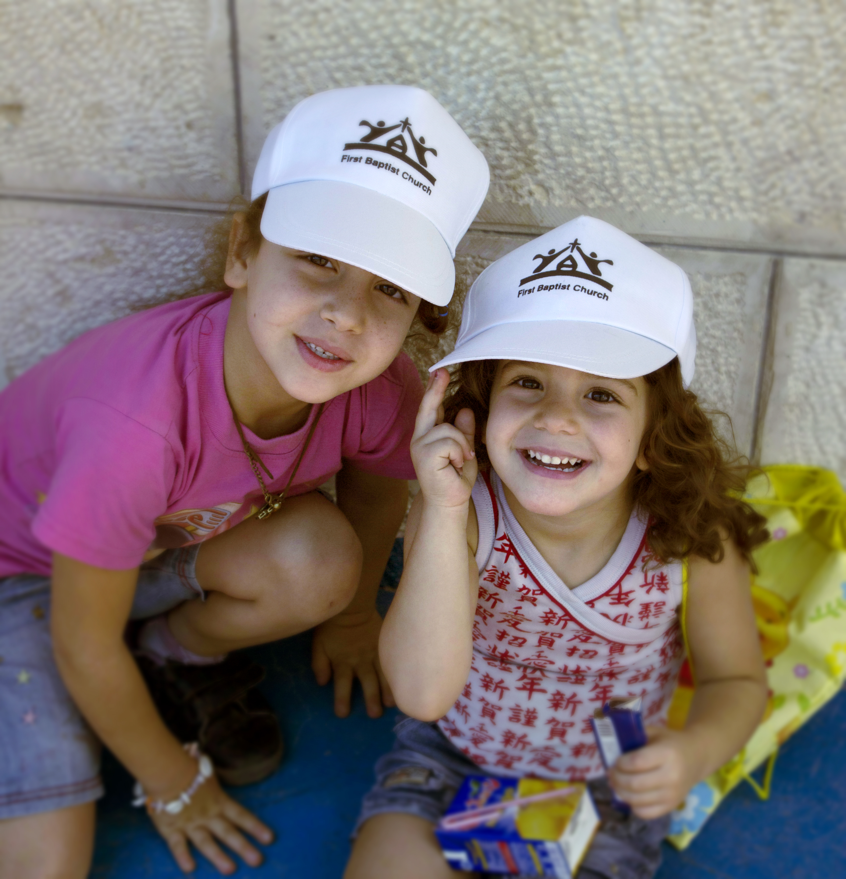 Two young girls at HLM Summer Camp, smiling while wearing white hats with the HLM logo.