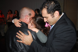 Pastor Steven Khoury praying over an Arab Christian man and his young daughter.