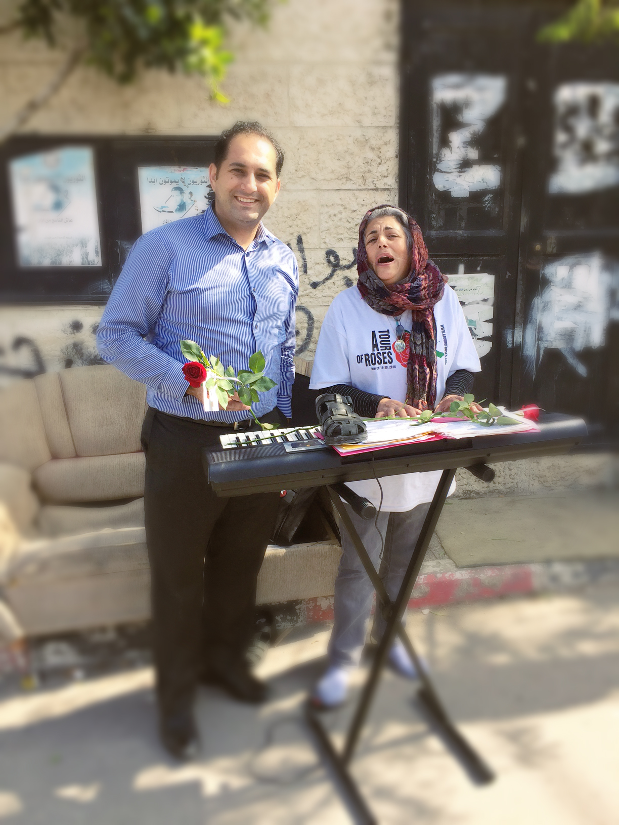 Pastor Steven Khoury standing next to a woman who is playing the keyboard and singing at Calvary Chu