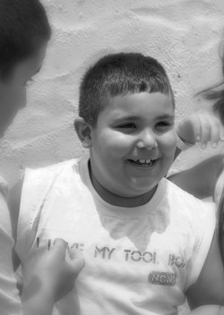A young boy, in a white sleeveless shirt smiling in black and white.