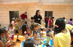 A couple of HLM staff members interacting with a group of young kids during an HLM program event.