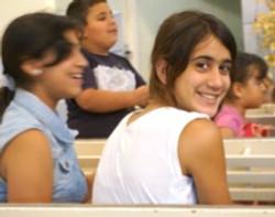 A few teenage Arab Christian girls sitting around a table during a gathering.