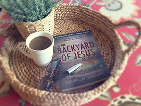 "A woven basket, with a cup of coffee, a small plant and the bok ""In the Backyard of Jesus"" by Steven Khoury inside."