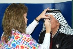 A woman performing an eye exam on a man wearing a keffiyeh.