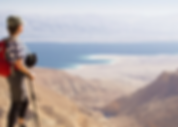 A woman, with red backpack and a hiking stick, overlooking a canyon with a body of water at the bottom in Israel.