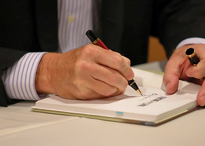 A man in a suit, writing a note with a pen in his notebook.