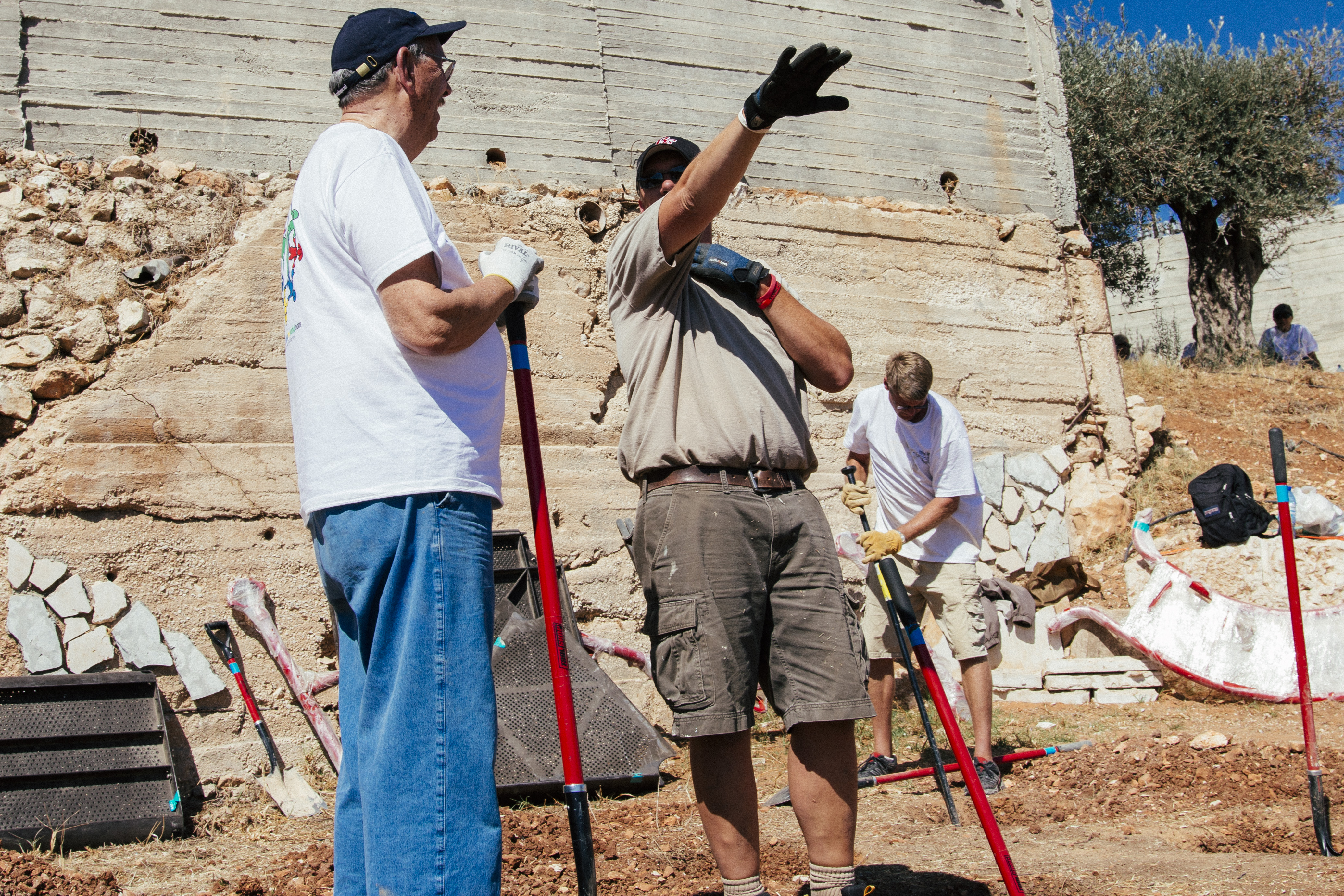 Two Holy Land Missions members, one pointing something out to another during an HLM construction mis