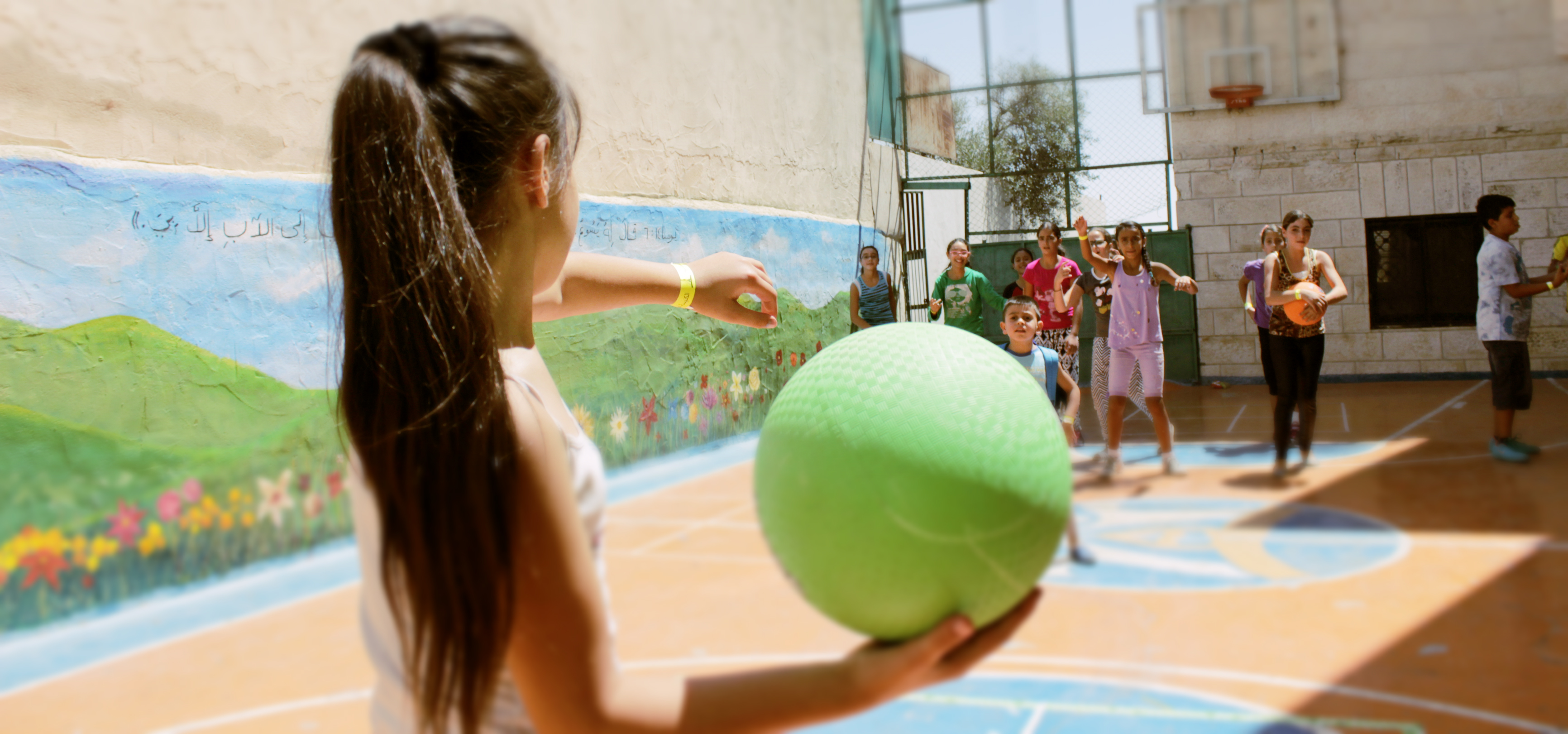 A young girl winding up to throw a green dodge ball to a group of kids.