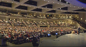 A large auditorium full of people during a conference.
