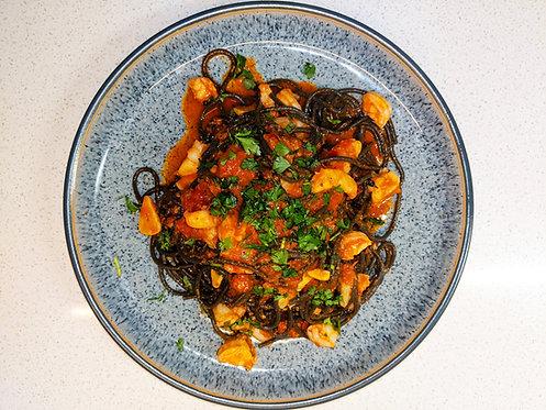 Squid ink spaghetti with prawns, 'nduja & tomato