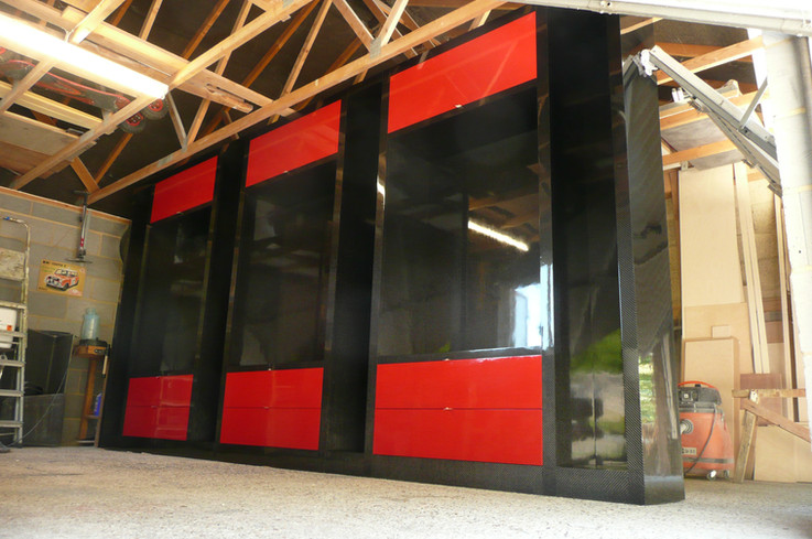 Free standing wall cabinet in gloss carbon and rosso red. Glass shelves and interior led lghting were added one piece installed.