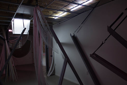 Installation made of blinds, metal, and bungee cords