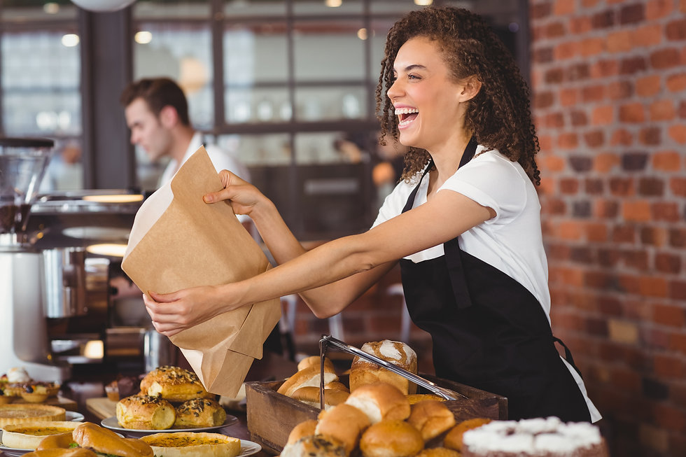 Smiling waitress giving paper bag to cus