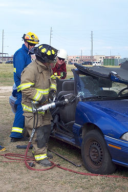 Firefighter using extrication tool on vehicle