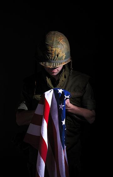 Vietnam War US Marine Holding Stars and Stripes Flag_edited.jpg