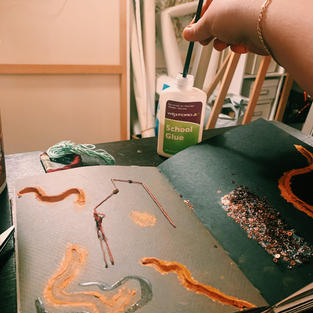 Adding a layer of glue to the clay to help keep it from crumbling off the page.
