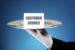 Butler or waiter holding a card reading customer service on a silver platter concept for first class