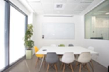 Ein Unterrichtsraum mit einem Tisch und acht Stühlen,einem Whiteboard und einer Klimaanlage.