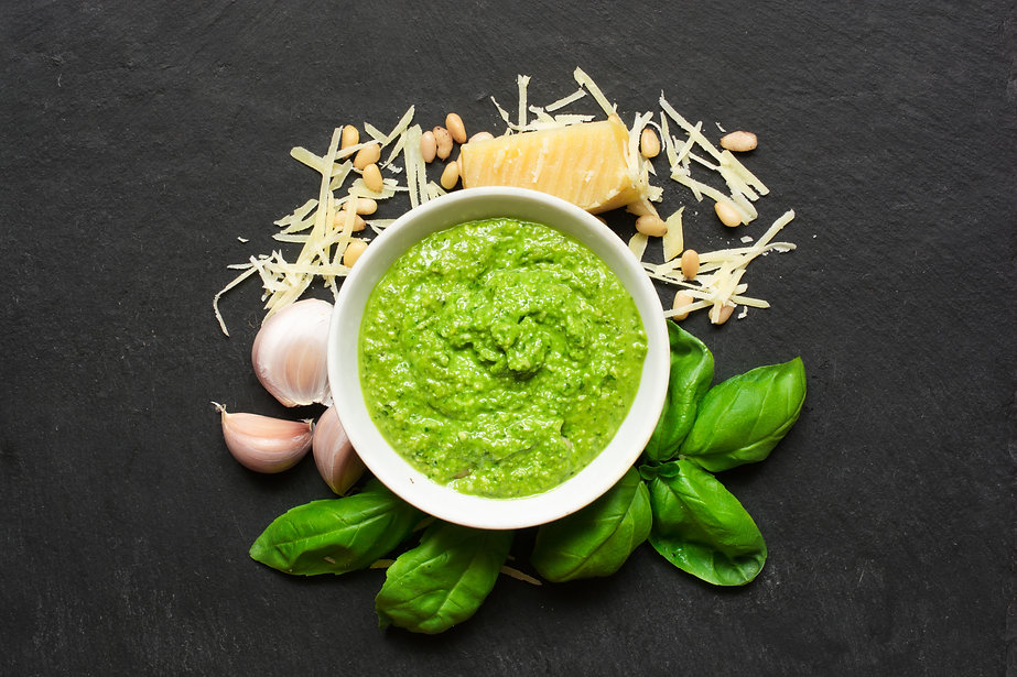 Pesto sauce in a bowl with pine nuts, parmesan and garlic over black stone background. top