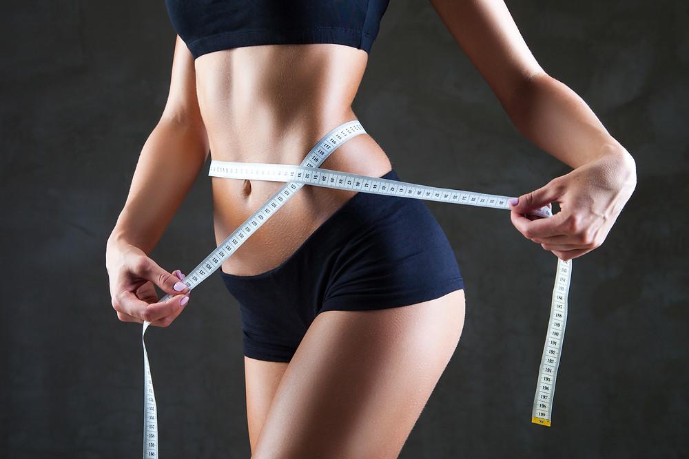 Mulher com fita métrica na cintura
