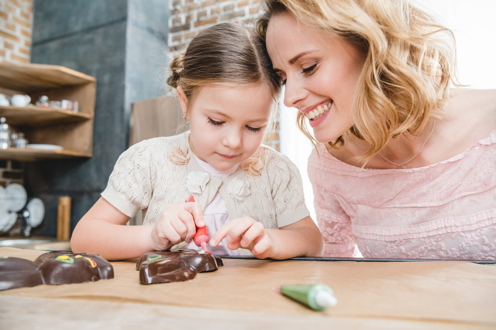 Mãe e filha decorando chocolates