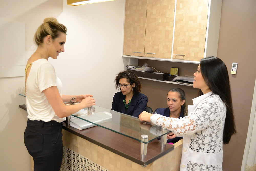 Recepção de clínica de estética com paciente, recepcionista e esteticista