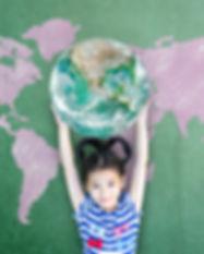 Asian kid student raising green globe on
