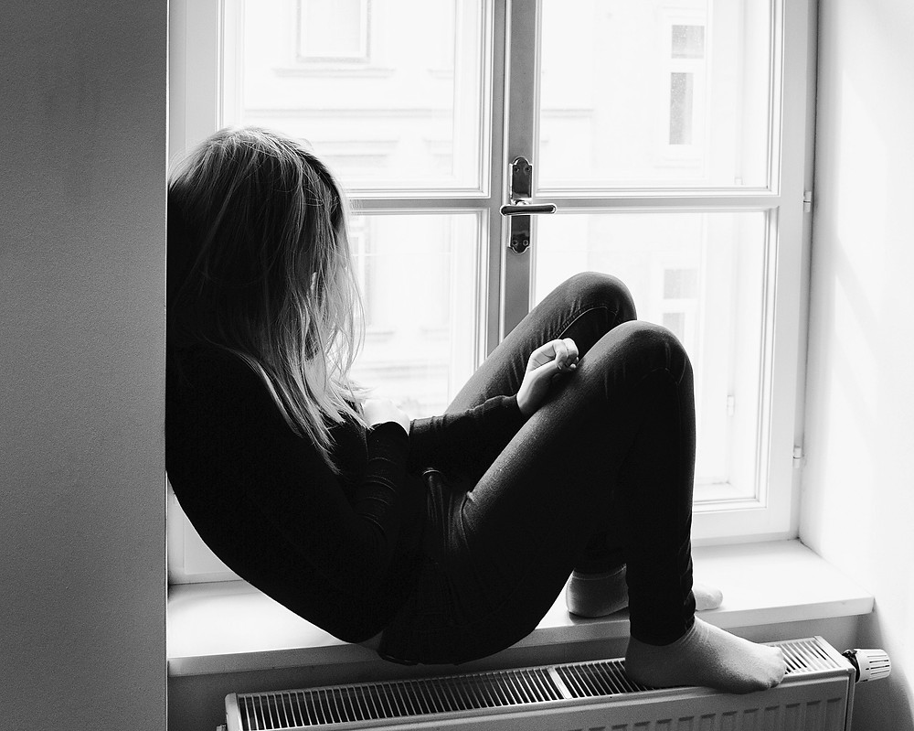 Teenaged girl sitting alone in a window sill, looking depressed.