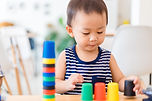 Little toddler boy playing stacking cups