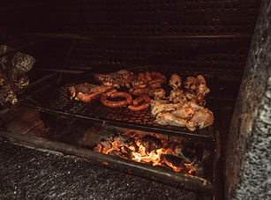 grilled-meat-on-black-charcoal-grill-at-