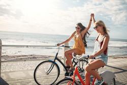 female-friends-enjoying-cycling-on-a-sum