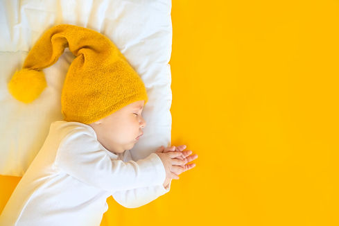 baby-sleeps-with-hat-yellow-background-w