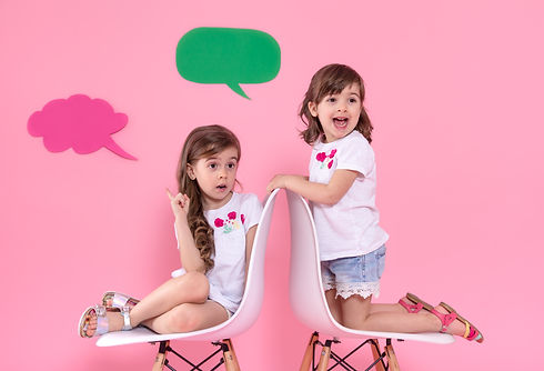 two-little-girls-colored-wall-with-speec