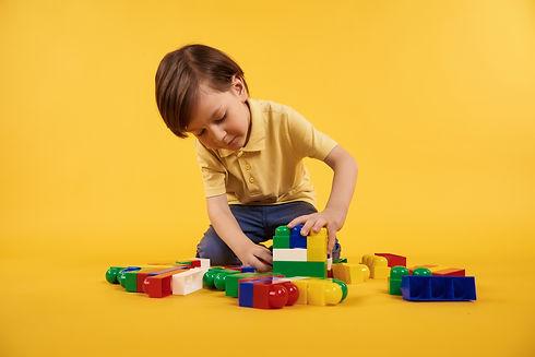boy-plays-with-plastic-toy-bricks-childr