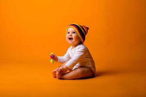 baby-boy-white-bodysuit-multicolored-hat