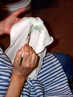 Hand painting glaze onto the bisq