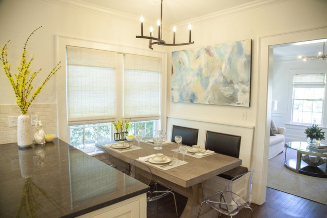 The family has their indoor meals in this spot with a modern fixture from The Home Depot and art by daughter Helen Kolker.