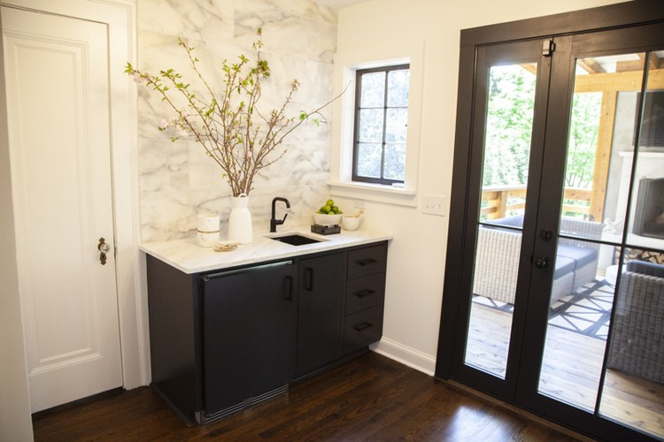 A bar, which was added in the renovations to the 1925 home, leads to the family's new outdoor space. The cabinets are painted Benjamin Moore's Black Beauty. Atlanta couple downsize to a Tudor-style home with modern lounge, spacious deck