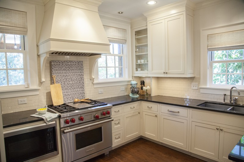 The renovated kitchen's white-and-black palette accentuates the lines of the cabinets, vent hood and Wolf appliances. The walls, trim and ceilings are painted Benjamin Moore's White Dove. Atlanta couple downsize to a Tudor-style home with modern lounge, spacious deck