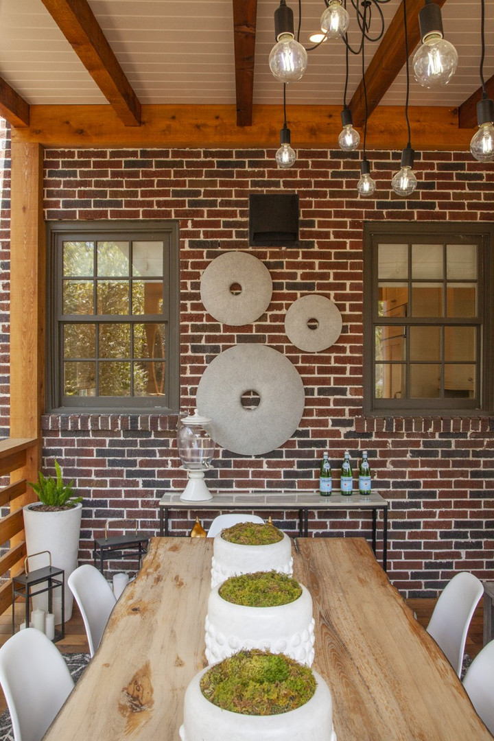 Sand dollar art from Janus et Cie, planters from CB2 and a tentacle chandelier from Poly & Bark bring modern elements to the cedar deck with a brick wall. The console is from Hayneedle. Atlanta couple downsize to a Tudor-style home with modern lounge, spacious deck