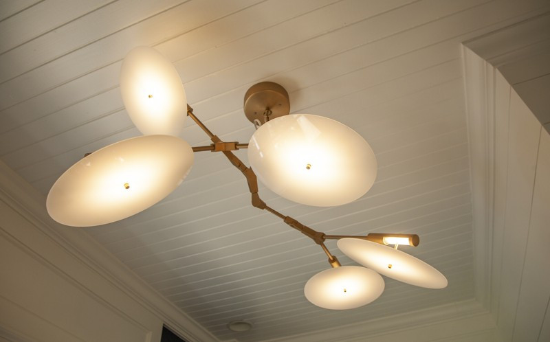 The modern halo chandelier by France & Son branches out from a beadboard ceiling.