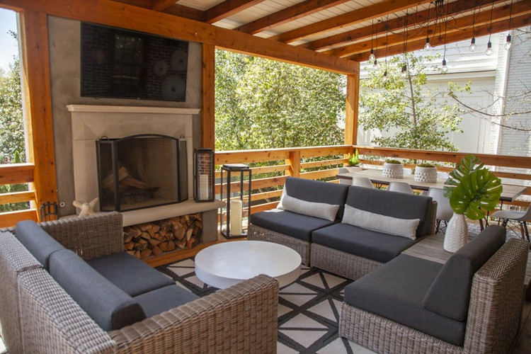 A cedar deck with a fireplace was added during 2017 renovations. In the covered area, the sectional is from Authenteak with Sunbrella cushions. A cement coffee table from CB2 is on a rug from Ballard Designs. The lanterns are from RH.