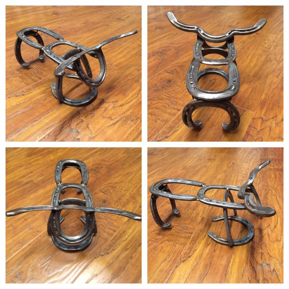 Metal bull statue made out of metal horse shoes.