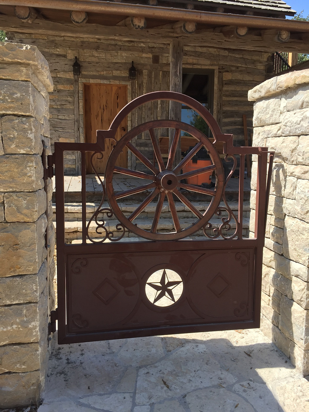 Wagon wheel metal gate restoration at a Comanche Peak home in Granbury, TX. Gate attached to rock fencing.