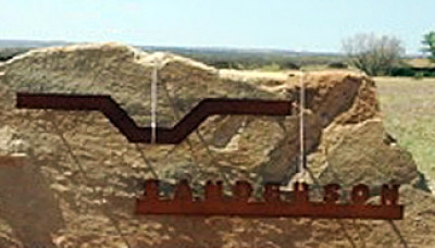 Sanderson ranch in Lubbock Texas. Metal sign adhered to a rock outside ranch gate