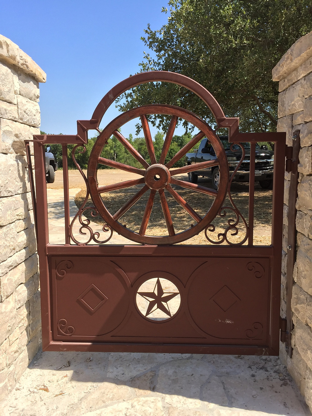 Finished wagon wheel gate attached to stone rock fenching in Comanche Peak in Granbury on a home restoration project