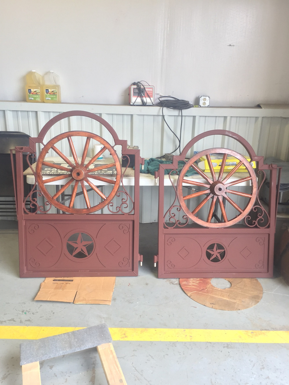Two wagon wheel gates on the Comanche Peak restoration project in Granbury, TX. Metal colored rustic leathertte, wood wheel stained and lacquered.