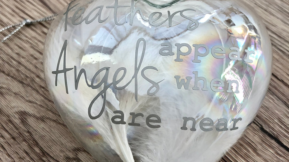 Feathers appear when angels are near glass heart decoration