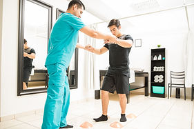 Young physiotherapist helping athlete to